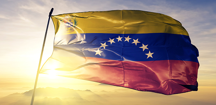 photo of Venezuelan flag with sun, sky and mountains in background